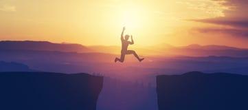 O homem que salta acima do penhasco nas montanhas imagens de stock royalty free