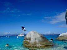 O homem que salta da rocha em Ilhas Virgens Imagem de Stock Royalty Free