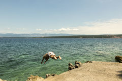 O homem que salta dentro ao mar Fotografia de Stock