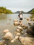 O homem que salta em rochas Fotos de Stock Royalty Free