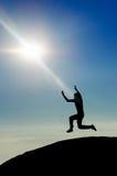 O homem que salta na silhueta do pico de montanha fotografia de stock