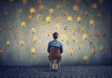 O homem que senta-se em uma cadeira tem muitas ideias que olham a parede que faz decisões fotos de stock