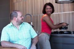 O homem que senta-se na mesa de cozinha e na mulher está cozinhando Fotografia de Stock