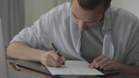 O homem que senta-se na tabela que corrige seu ensaio escreveu no papel em casa Conceito da profissão, escritor, redator, editor vídeos de arquivo