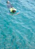 O homem que snorkeling toma a foto no oceano limpo Fotos de Stock