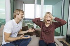 O homem que tenta falar como a mulher grita para fora alto na sala de visitas em casa fotos de stock