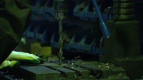O homem que trabalha na loja no trabalho com metal Feche acima do metal da perfuração do bocado de broca com os coordenadores no  filme