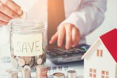 O homem que usa a calculadora salvar o dinheiro para o custo home imagens de stock