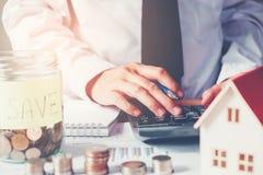 O homem que usa a calculadora salvar o dinheiro para o custo home foto de stock
