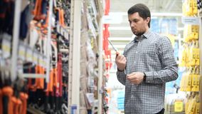 O homem quer comprar uma chave de fenda na loja do hardware video estoque