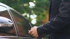 O homem recebe chaves ao automóvel luxuoso do negociante no salão de beleza, movimentação do teste, fim acima video estoque