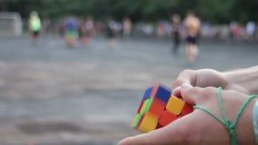 O homem recolhe nas mãos do cubo do Rubik vídeos de arquivo