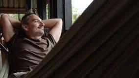 O homem relaxa em uma rede video estoque