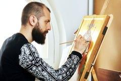 O homem religioso do pintor pinta um ícone novo Fotografia de Stock Royalty Free