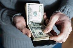 O homem remove ervas daninhas fora do dinheiro fora de sua carteira Homem rico que conta seu dinheiro Imagem de Stock Royalty Free
