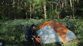 O homem remove uma trouxa perto da barraca Tentativa encontrar algo Amanhecer na floresta vídeos de arquivo