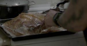 O homem removeu uma galinha cozida do saco do forno e do forno do corte vídeos de arquivo