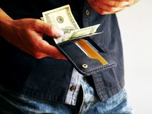 O homem retira uma carteira com 100 dólares imagens de stock royalty free