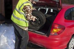 O homem retira uma roda de reposição do tronco de um carro que veste uma veste reflexiva Imagem de Stock Royalty Free