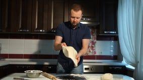 O homem rola a massa na mesa de cozinha com um pino do rolo filme
