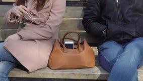 O homem rouba o telefone de um saco do ` s da mulher no parque vídeos de arquivo