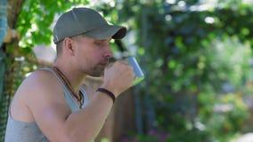 O homem rural considerável no calor aviva a sede com água da caneca do ferro vídeos de arquivo