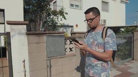 O homem sério adulto está andando na rua com o smartphone nas mãos, vista dianteira vídeos de arquivo