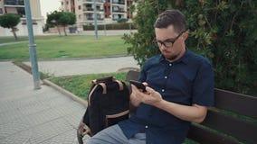 O homem sério está sentando-se em um banco na aleia no parque da cidade, datilografando no telefone celular vídeos de arquivo