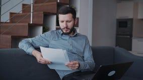 O homem sério está sentando-se no sofá e está verificando-se a informação usando o portátil moderno da tecnologia vídeos de arquivo
