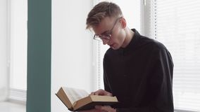 O homem sério novo está lendo uma Bíblia contra uma janela filme