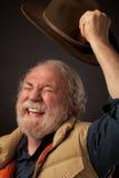 O homem sênior acena alegre o chapéu no ar Imagens de Stock Royalty Free