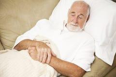 O homem sênior dorme no sofá Imagens de Stock Royalty Free