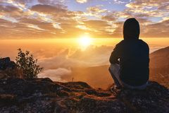 O homem só que senta-se em uma montanha para o nascer do sol de observação vê conceito apenas, do sucesso e da paz em morno fotografia de stock royalty free