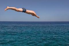 O homem salta no mar em um dia ensolarado Fotos de Stock Royalty Free