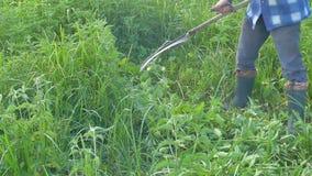 O homem sega a grama verde usando uma foice video estoque