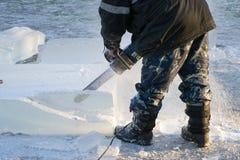 O homem segura a serra de cadeia do gelo Foto de Stock