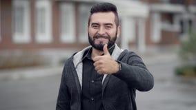 O homem seguro com barba está estando fora no dia, está olhando a câmera, está sorrindo e está mostrando os polegares acima vídeos de arquivo