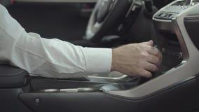 O homem seguro não reconhecido que senta-se no veículo e inspeciona comprou recentemente auto do concessionário automóvel Carro filme