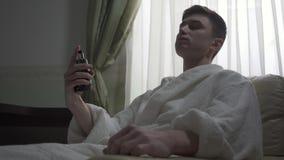 O homem seguro no roupão branco perfuma-se ao sentar-se na poltrona em casa e ao olhar na câmera Manhã vídeos de arquivo
