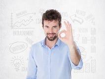 O homem seguro novo mostra com sua mão que tudo é bom Fotografia de Stock Royalty Free