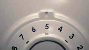 O homem seleciona o programa da lavagem girando o seletor da máquina de lavar filme