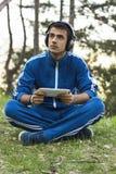 O homem senta-se com a tabuleta na grama Foto de Stock
