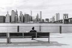 O homem senta-se e admira-se da baixa de New York Imagens de Stock Royalty Free