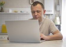O homem senta-se em sua cozinha com um port?til foto de stock royalty free
