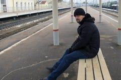 O homem senta-se em um banco Imagem de Stock Royalty Free