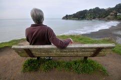 O homem senta-se em um banco acima do oceano Imagens de Stock Royalty Free