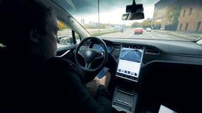 O homem senta-se em um carro elétrico que vai no piloto automático Condução automatizada futurista do auto do carro elétrico vídeos de arquivo