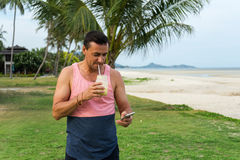 O homem senta-se em uma grama no país tropical da ilha Samui, o batido das bebidas do homem Imagens de Stock