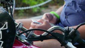O homem senta-se em usos retros do velomotor telefona no parque, conceito do moderno Feche acima das mãos 3840x2160 filme