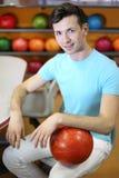 O homem senta-se na tabela perto das prateleiras com esferas Fotos de Stock Royalty Free